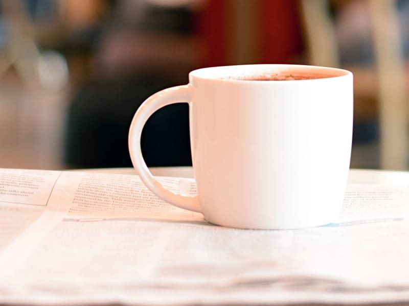 Coffee cup with newspaper on the table